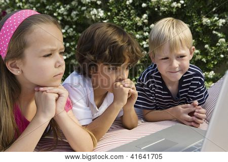 Preadolescent friends seriously looking at laptop in lawn
