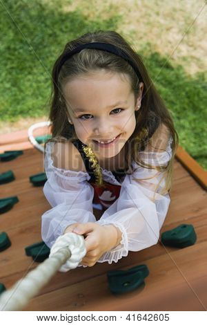 High angle view of a happy preadolescent girl hanging on a rope