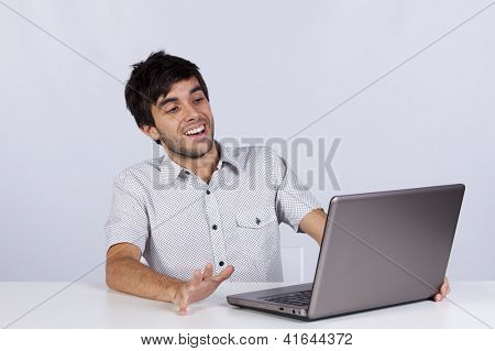 young man shocked with something he see on his laptop computer