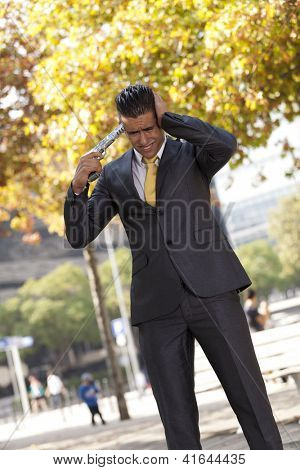 Stressed businessman with a gun pointing to his head