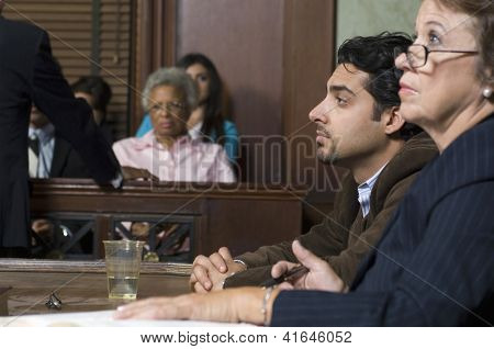 Side view of advocates with client during prosecution in court house