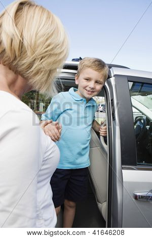 Mature woman helping grandson get down from minivan