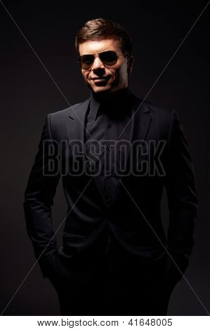 stylish smiley man in black formal wear and sunglasses. studio shot over dark background