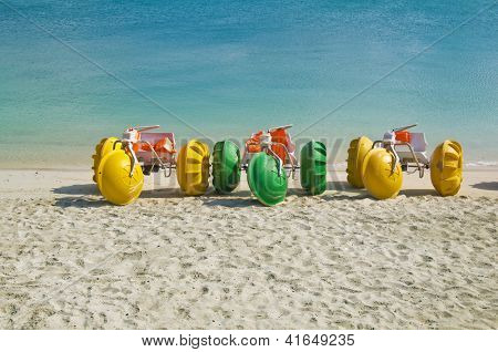 Colorful water bikes parked on the beach