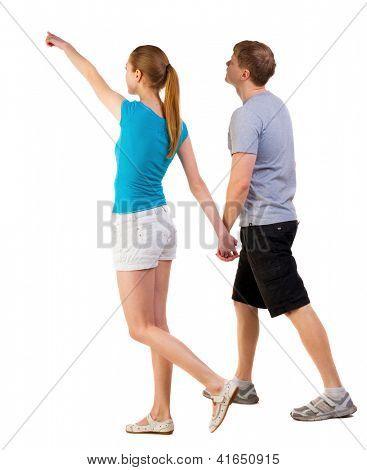 Vista traseira do pé apontando jovem casal (homem e mulher). turistas indo em shorts considerando att