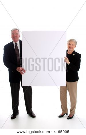 Senior Couple Holding Sign
