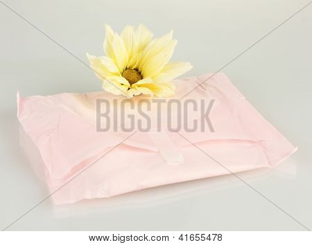Panty liner in individual packing and yellow flower isolated on white