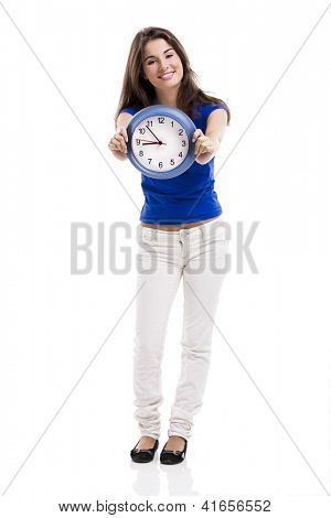 Causal young woman holding a clock, isolated over a white background