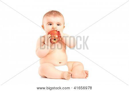 A 9 months old baby boy sitting and eating a red apple isolated on white background