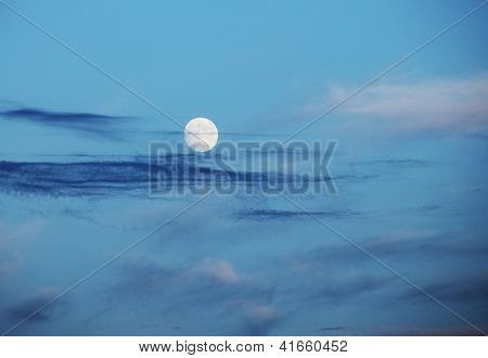 Full moon over evening sky with thin clouds