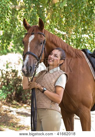 Portrait Of A Beautiful Horsewoman Standing With Horse Outdoors