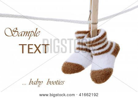 Baby booties hanging on clothesline on white background with copy space.