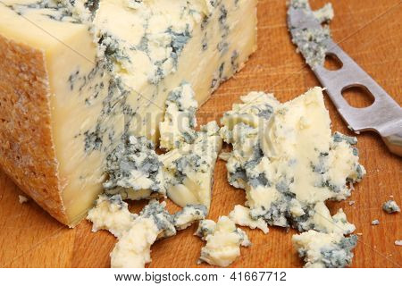 Stilton cheese on cheeseboard. Shallow DoF, focus on centre of image.