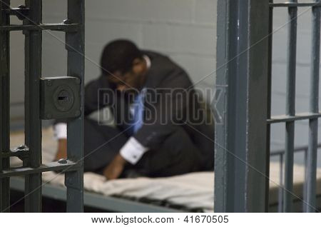 A depressed businessman sitting in jail