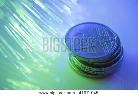 Euro coins on fiber optics background