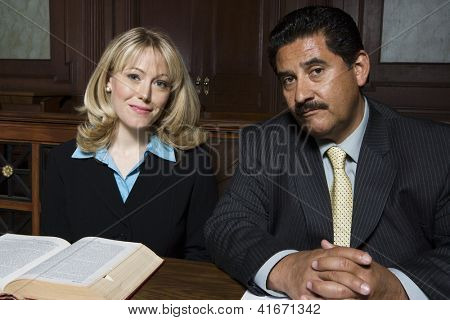 Portrait of an advocate sitting with colleague in courtroom