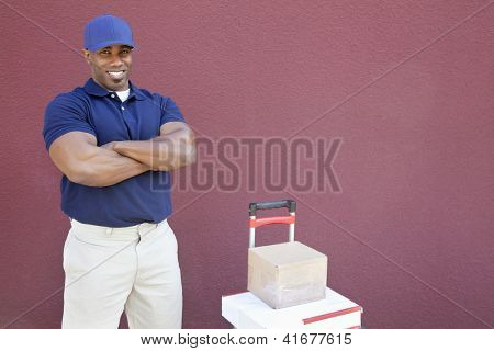 Muscular African American man standing with arms crossed and hand truck over colored background
