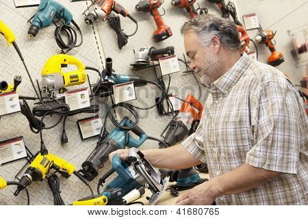 Side view of middle-aged salesperson looking at electric saw