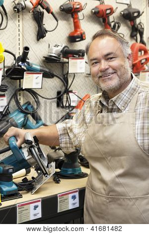 Happy salesperson with electric saw in hardware store