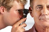 stock photo of otoscope  - Doctor Examining Male Patient - JPG