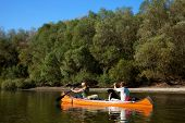 picture of canoe boat man  - Young couple enjoying a trip in a canoe - JPG