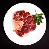 stock photo of beef shank  - Raw beef with bone on white plate - JPG