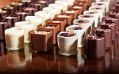 foto of truffle  - Rows of dark milk and white chocolate truffle cups displayed on a shiny wooden surface - JPG
