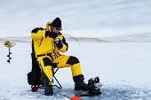 picture of auger  - Ice fisherman with a fish on his line - JPG
