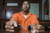 image of prison uniform  - African American prisoner fettered with handcuffs sitting in courtroom - JPG