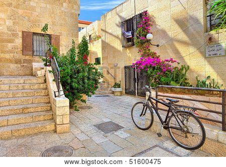 Bicycle on narrow street among typical stoned houses of jewish quarter in Old City of Jerusalem, Israel.