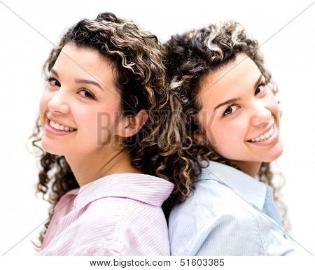 Beautiful twins smiling - isolated over a white background