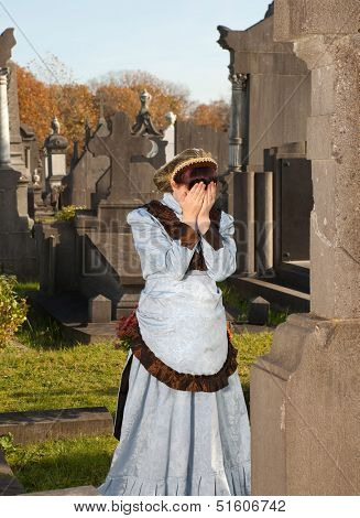 Crying widow in Victorian dress at a graveyard
