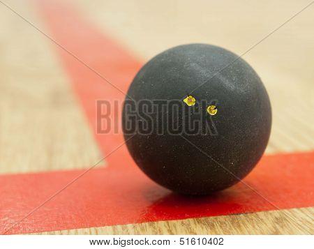 Black squash ball on t-line
