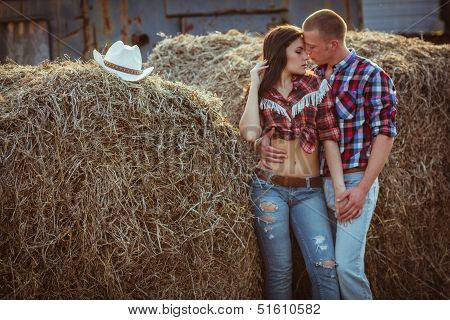 couple embracing near hay