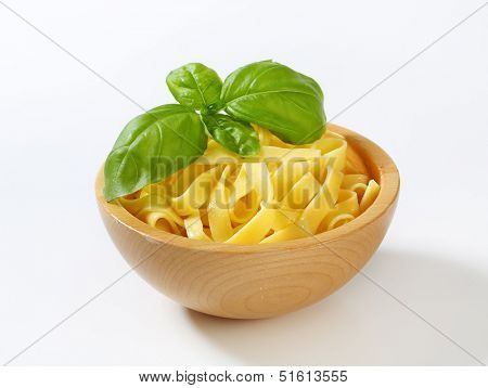 boiled spaghetti served with basil on a wooden bowl