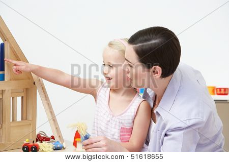 Pre-School Teacher And Pupil Playing With Wooden House