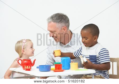 Pre School Children Enjoying Tea Party With Teacher