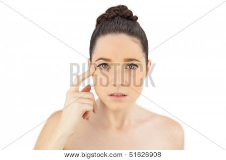 Natural model showing crows feet while posing on white background