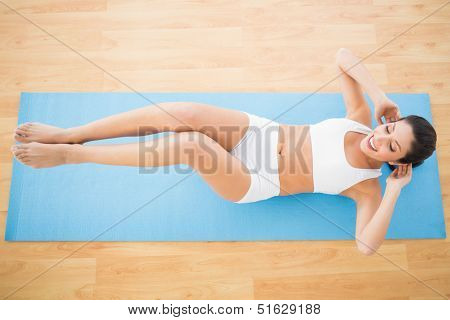 Fit woman doing abdominal crunches at home on wooden floor