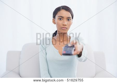 Serious woman sitting on sofa in bright living room changing tv channel