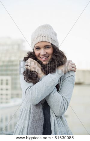 Pretty young brunette shivering outside on a cloudy day