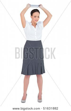 Angry businesswoman throwing her tablet pc while posing on white background