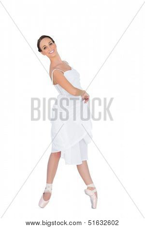Smiling young ballet dancer standing on her tiptoes on white background