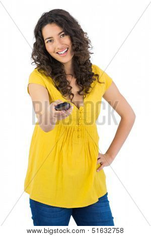 Smiling curly haired pretty woman on white background changing channel with remote