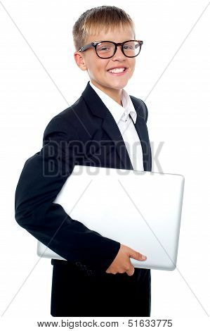 Bespectacled Young Boy Carrying A Laptop