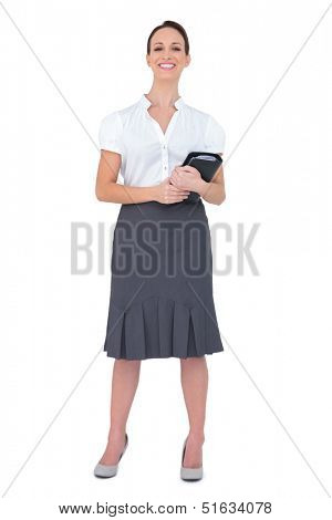 Cheerful businesswoman holding datebook on white background
