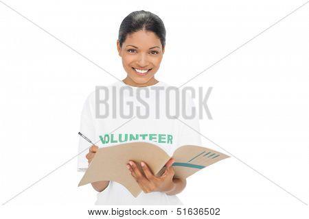 Smiling model wearing volunteer tshirt on white background writing
