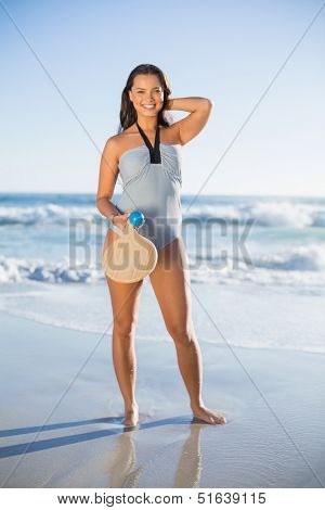 Happy woman in one piece swimsuit posing with beach racket on a sunny day