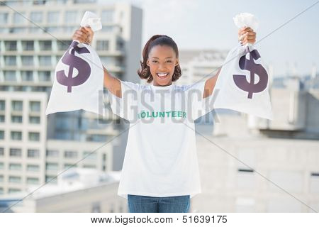 Happy volunteer woman holding money bags outdoors on urban background