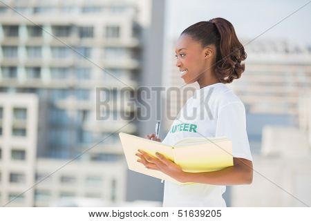 Cheerful altruist woman holding notebook outdoors on urban background